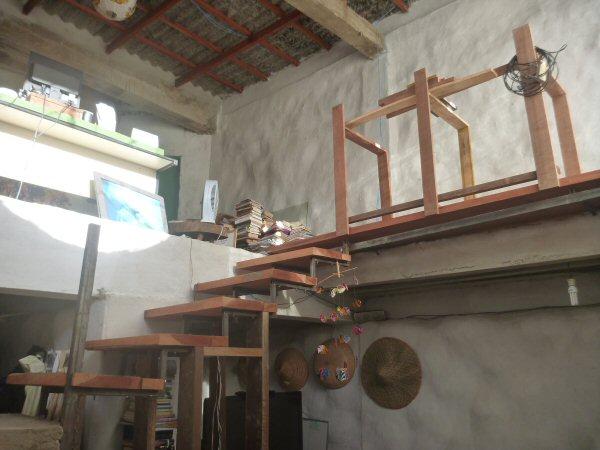 A escada está sendo feita de madeira e ferro. Ela vai para o mezanino, onde fica a sala da Vera. A estante, que está sendo feita,serve de guardacorpo e onde serão colocados alguns livros.